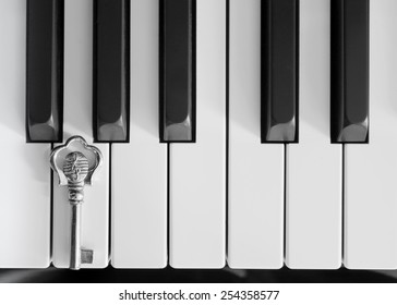 Piano keys and a silver key with G-clef musical symbol; black and white photo