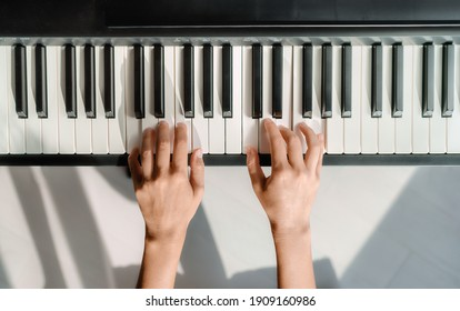 Piano learning chords at home - woman playing digital keyboard with online music lesson. Top view of musician hands on keys.