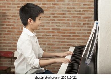 piano lesson, Asian boy kid activity playing piano with notes, smiling