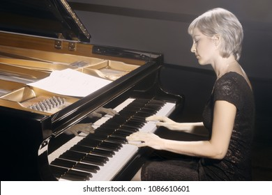 Piano player. Pianist woman playing piano. Classical musician closeup with grand piano