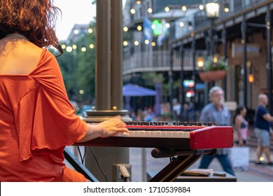 Piano player playing electric piano (showing motion) on Fulton Street in New Orleans, Louisiana, USA