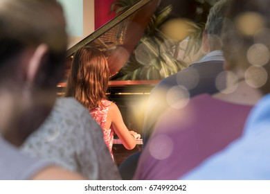 PIANO RECITAL BY A GIRL WITH PARENTS AUDIENCES WATCHING FROM BEHIND