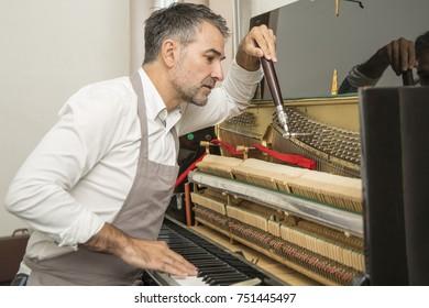 Piano technician repairing the piano