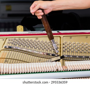 A Piano tuner is tuning upright piano, The right hand of piano tuner is tuning upright piano. Tune in-house piano.