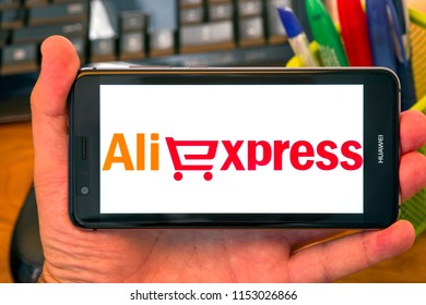 PIATRA NEAMT, ROMANIA - JULY 30, 2018: Hand holds a mobile phone with Aliexpress logo on the screen, office background.