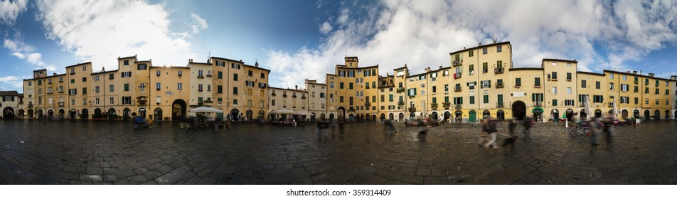 Piazza Anfiteatro, Lucca. 360 degrees panoramic view made by merging multiple vertical shot. Curious elliptical square surrounded by medieval houses. Lens flare due to the photomerge.