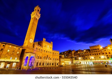 Piazza del Campo in the historic center of Siena, Tuscany, Italy, with Palazzo Pubblico and Torre del Mangia tower at late evening