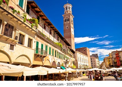 Piazza delle Erbe in Verona street and market view with Lamberti tower, tourist destination in Veneto region of Italy