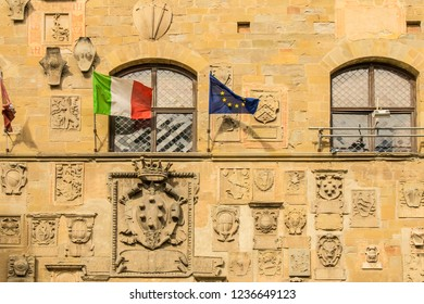 Piazza Grande, Arezzo, Tuscany/Italy-September 19, 2017:Plaques and flags on wall of  town hall in Piazza Grande