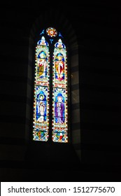 Piazza San Francisco, Siena,Italy : May 24, 2011: Colorful large arched stained glass window of Basilica di San Francesco, Gothic style basilica church with biblical figures and illustrations.