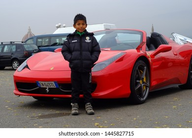 Piazzale Michelangelo, Florence, Tuscany. Italy - circa April 2017 - Red luxury italian Ferrari car parked with latin boy beside it. Early spring season.