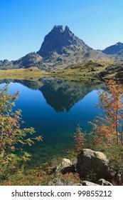 Pic du Midi d'Ossau reflecting in a beautiful lake Lac Roumassot (Lacs d'Ayous), Parc national des Pyrenees, Aquitaine, France.