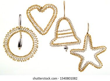 A pic of four beaded Christmas tree decorations, circle, heart, bell and star