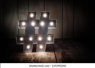Pic of lighted hashtag symbol on a wooden background