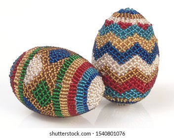 A pic of two very colourful beaded eggs Christmas tree decorations