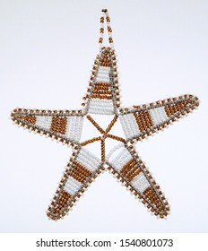 A pic of a white and gold beaded star Christmas tree decorations
