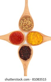 Piccalilli, sweet vegetable relish,  chili sauce, and wholegrain mustard in wooden spoons isolated over white background.