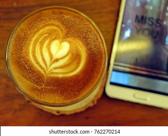 Piccolo Latte Coffee with Heart Pattern and Smart Phone have Picture 'Miss You' in Concept love and Valentine's Day