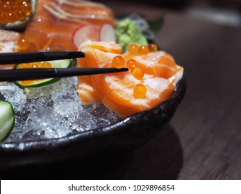 Pick fresh sliced Salmon sashimi with chopsticks served with seaweed, wasabi and salmon roe in black bowl. Japanese traditional food with selective focus.