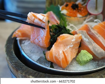Pick fresh sliced Salmon sashimi with chopsticks served with seaweed, wasabi and salmon roe in wooden bowl . Japanese traditional food with selective focus.