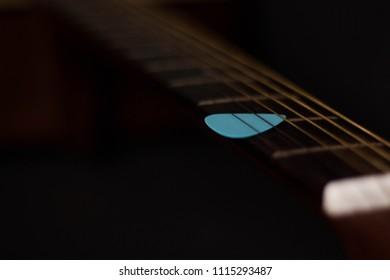 pick & guitar fretboard, on old wood + vintage filter for music background