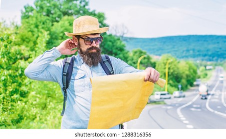 Pick up local map. Tourist backpacker looks at map choosing travel destination at road. Around the world. Find map large sheet of paper. Allow recognize enough details to walk somewhere if get lost.