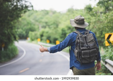 Pick me up. Man hitchhiking on the side of the road. Man try stop car thumb up. Hitchhiking one of cheapest ways traveling.