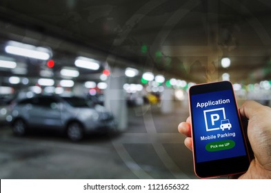 pick me up, mobile smart phone in hand using application for intelligent car park on blurred parking car indoor background, mobile auto parking, online technology and internet connection concept
