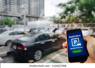 pick me up, mobile smart phone in hand using application for intelligent car park on blurred parking car outdoor background, mobile auto parking, online technology and internet connection concept