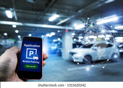 Pick me up, mobile smart phone in hand using application for intelligent car park with digital hologram on blurred parking car background, mobile auto parking, network and online technology concept
