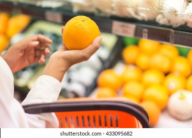 Pick orange,Women hand pick up orange in supermarket.