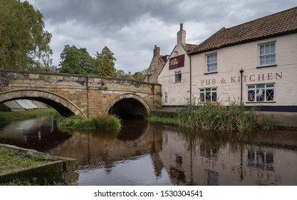 Pickering, England - October 12th 2019: The bridge carrying Bridge Street over Pickering Beck, adjacent to The Rose Pub and Kitchens.