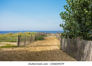 A picket fence along the sand dunes leads to the neach in Keansburg New Jersey.