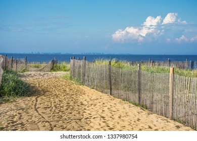 A picket fence along the sand dunes leads to the beach in Keansburg New Jersey.