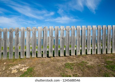 Picket fence constructed of bare unpainted timber on barren ground with blue sky and clouds.