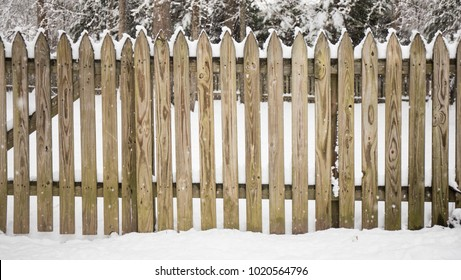 A picket fence covered with snow and the snow is still coming down.