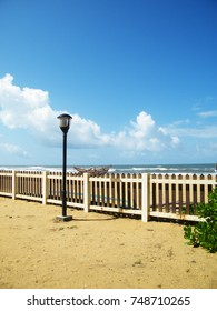 Picket fence and sunflowers beach summer home.Beach with windbreak wooden fence.Coast line wooden fence for hotel buildings.Sri Lankan beach fence.
