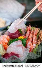 Picking Premiwith chopstick, Tai fish sashimi, Ebi sashimi, Maguro sashimi, salmon sashimi - Dark background warm tone image