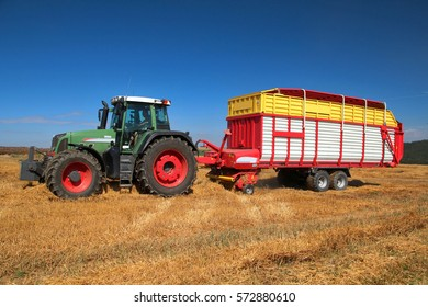 Picking up straw from barley stubble, summer grain harvest, straw used for bedding and feeding of cows and pigs, bio agriculture, side perspective