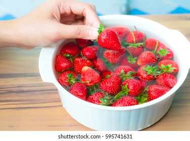 picking strawberry in a bowl on wooden background