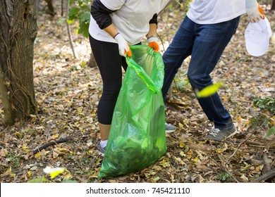 Picking up trash in the forest. Ecology people cleaning the park with green garbage bag. Unrecognizable people.