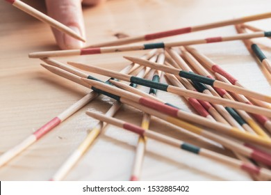 Picking up a wood pick-up stick from a random pile in Mikado game