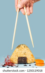 Picking up yellow rise onigiri sushi with chopsticks. Closeup concept of Japanese food eating, viewed from the side on blue background