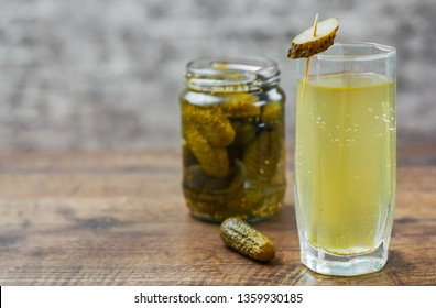 Pickle juice in glass and a can of pickled cucumbers on wooden table background