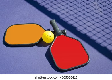 Pickleball - 2 Paddles and A Ball Lying on Court Near Net Shadow