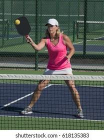 Pickleball Action - Attractive Senior Women Player Hitting Ball At Net