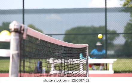 A pickleball goes over the net during a tournament.