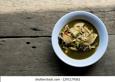 Pickled bamboo shoot with mushroom curry on wooden is northeast food of Thailand.