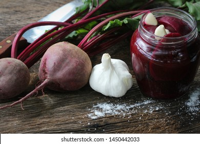 Pickled beets in the jar on a dark wood background .