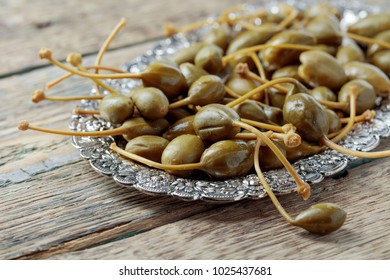 Pickled caper berries in metal dish . Edible fruits of Capparis . Berries are used as garnish.Old wooden background.